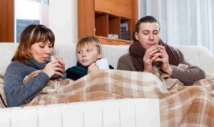 freezing family of three with cups of tea warming near warm radiator in home